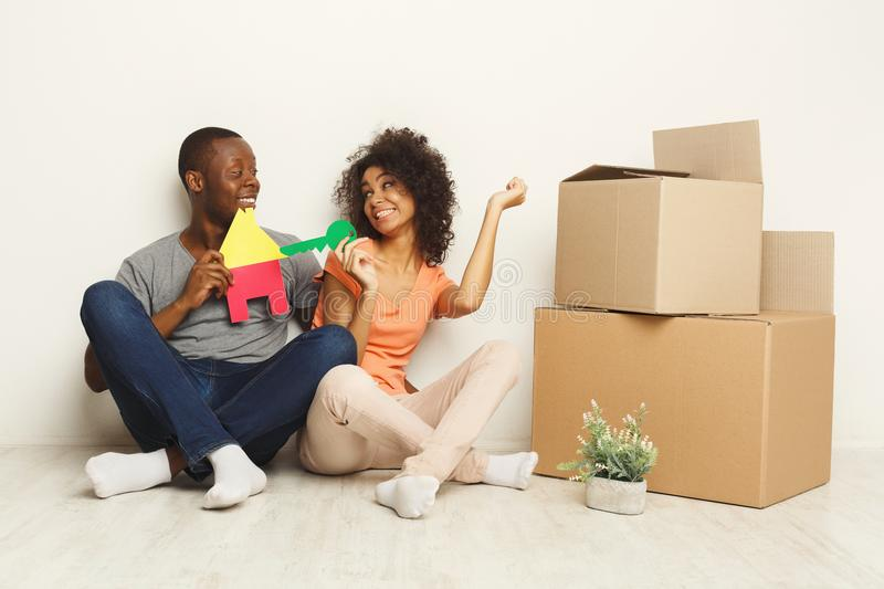 Black couple sitting on floor at new apartment stock photography