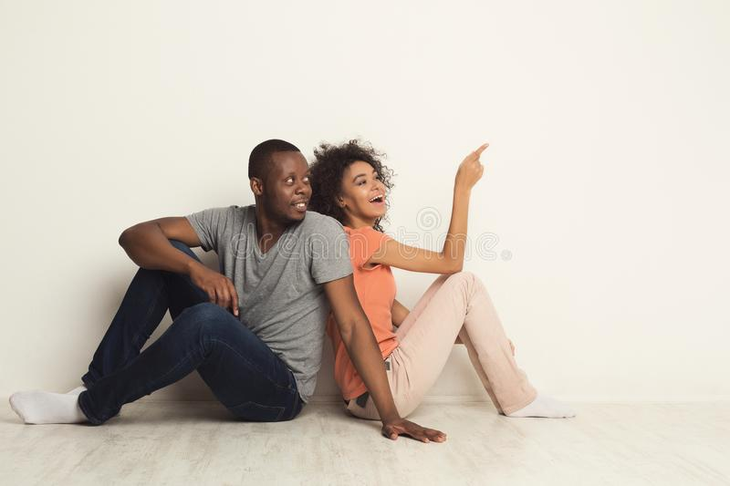 Black couple looking up sitting on floor royalty free stock photo