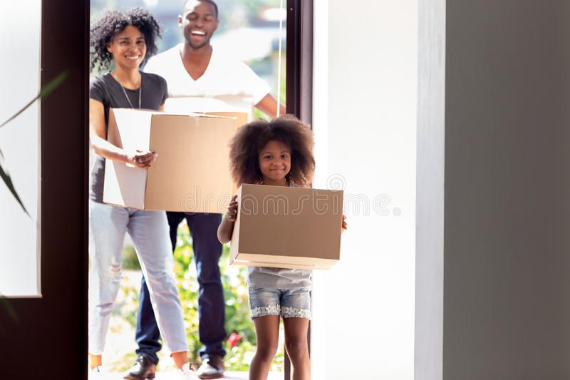 Happy African American family with daughter entering in new house stock image