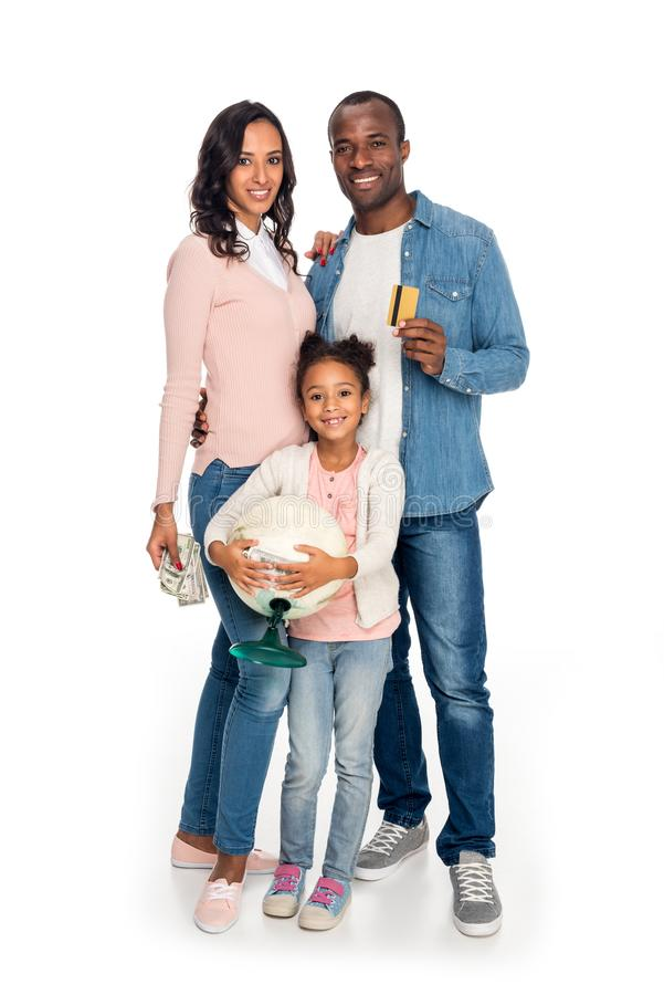 happy african american family with globe, money and credit card smiling at camera royalty free stock image