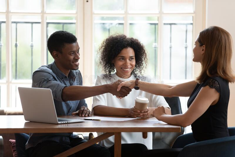 Happy African American family handshaking with realtor at meeting royalty free stock photo
