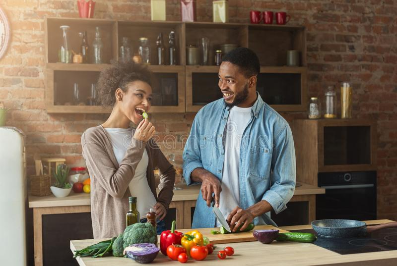 Happy african-american couple cooking in loft kitchen. Happy african-american family at kitchen. Black couple cooking in loft interior royalty free stock photo