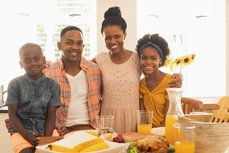 Happy African American family looking at camera on dining table royalty free stock photos