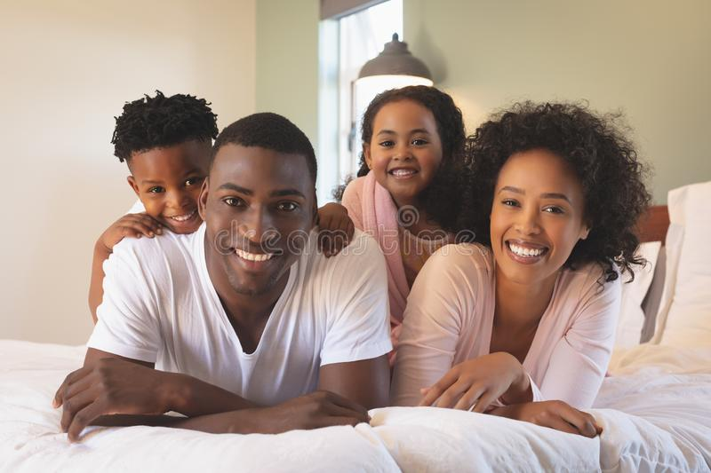 Happy African American family lying on bed and looking at camera royalty free stock photos