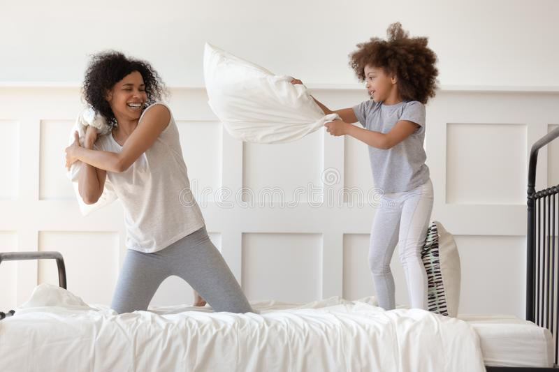 Happy african mom and daughter having pillow fight on bed. Happy african american family mixed race mom and little cute daughter having fun pillow fight on bed royalty free stock image
