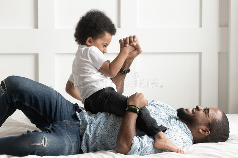 Happy african dad laughing playing with little son on bed stock photo