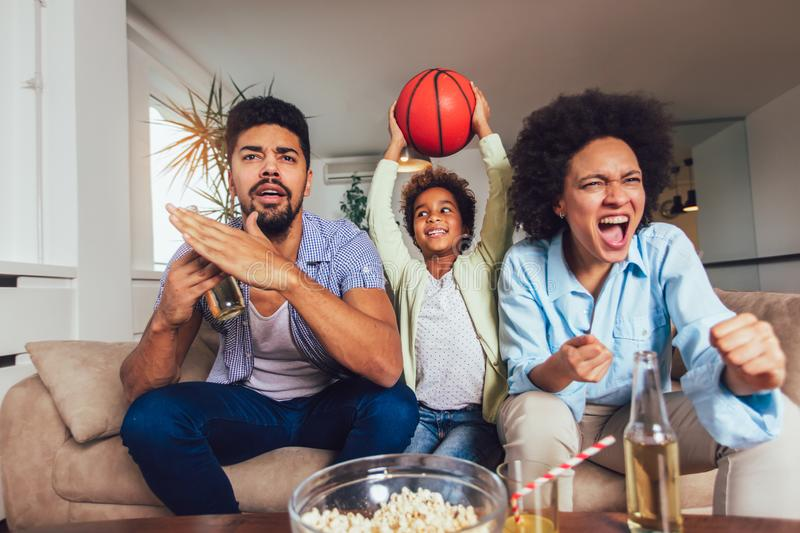 African American family of three watching tv and cheering sport games on sofa at home. Happy African American family of three watching tv and cheering sport stock photography
