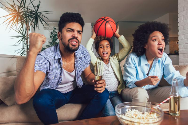 African American family of three watching tv and cheering sport games on sofa at home. Happy African American family of three watching tv and cheering sport stock photo