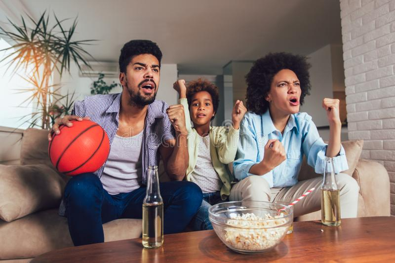 African American family of three watching tv and cheering sport games on sofa at home. Happy African American family of three watching tv and cheering sport royalty free stock photo