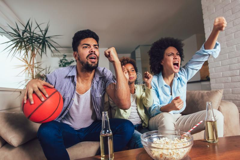 African American family of three watching tv and cheering sport games on sofa at home. Happy African American family of three watching tv and cheering sport stock photos