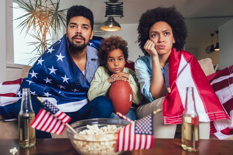African American family of three watching tv and cheering sport games on sofa at home. Happy African American family of three watching tv and cheering sport royalty free stock images