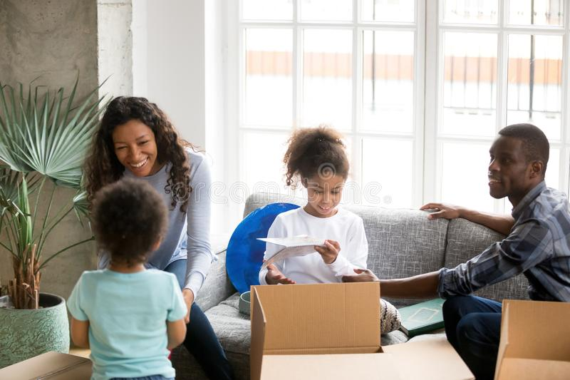 Happy African American family unpacking boxes, just moving royalty free stock photos