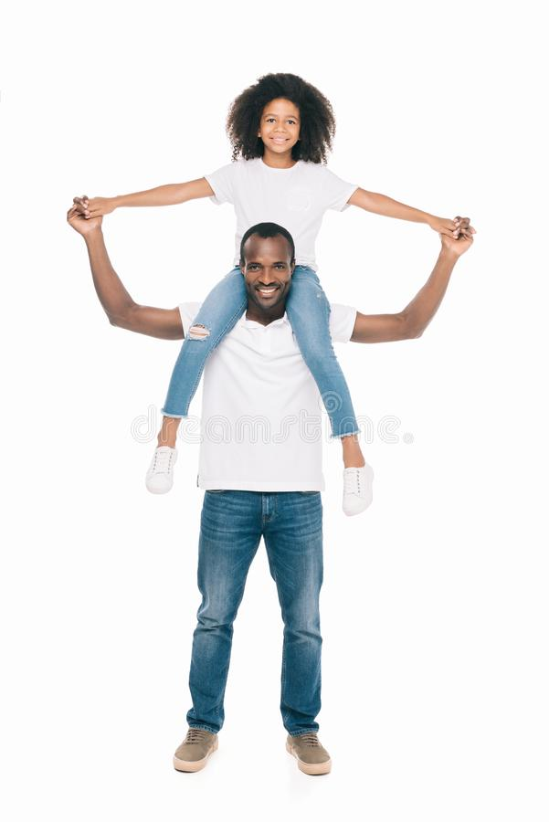 happy african american father carrying daughter on neck and smiling at camera stock photos