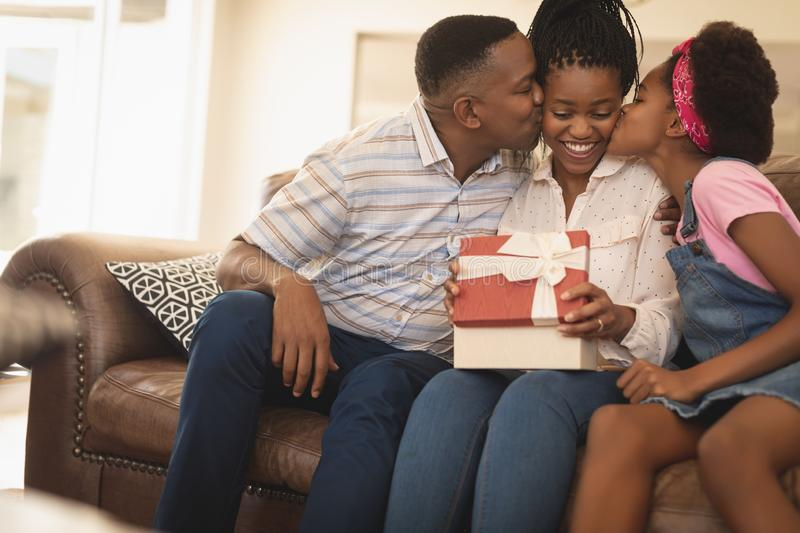 Happy African American father and daughter kissing mother on cheeks royalty free stock image