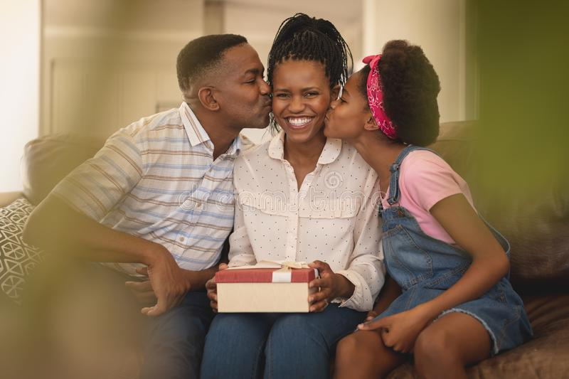 Happy African American father and daughter kissing mother on cheeks stock images
