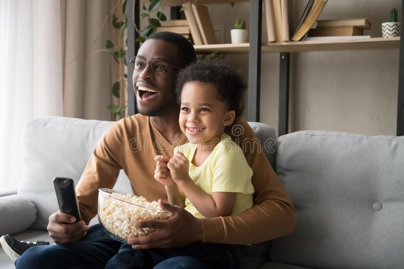 Happy African American father with son watching tv, eating popcorn. Happy African American father with toddler son, family watching tv, cartoons or football vector illustration