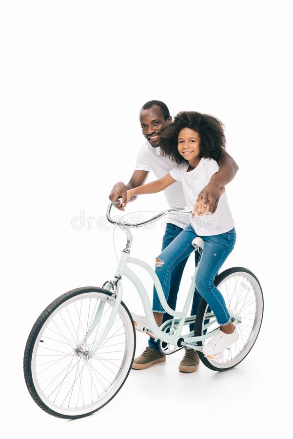 happy african american father teaching cute smiling daughter riding royalty free stock images