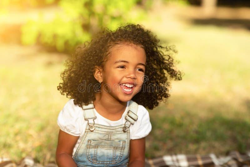 Happy african-american girl walking in park, free space. Happy african-american girl sitting on blanket and laughing, walking in park, free space stock photos