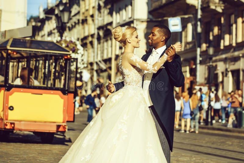Happy african American groom and cute bride dancing on street stock photos