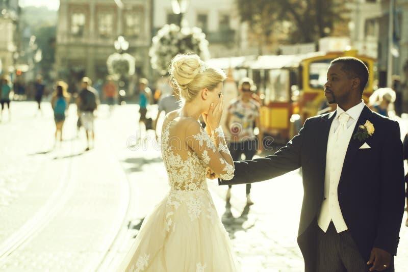 Happy african American groom and cute bride dancing on street stock image