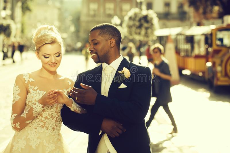 Happy african American groom and cute bride walking on street stock photos