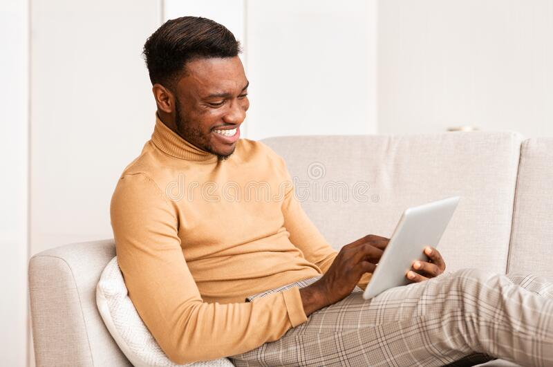 Happy Guy Using Tablet Computer Sitting On Couch At Home royalty free stock photography