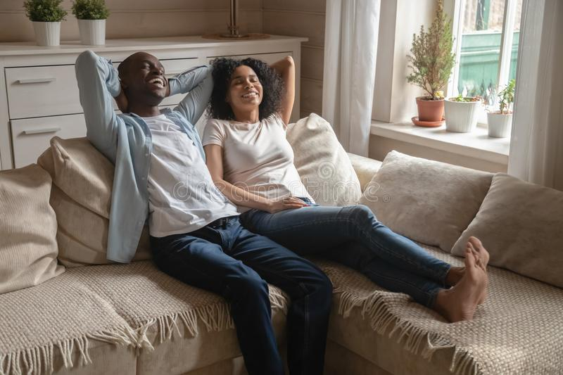 Happy biracial couple lying on couch dreaming together stock image