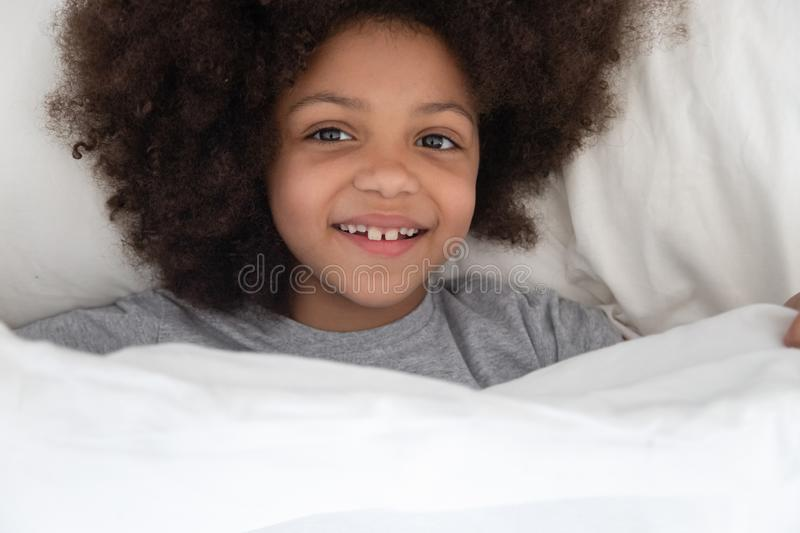 Happy african american kid girl waking up in the morning. Top above view happy african american kid girl lying on pillow in bed under blanket, waking up in the royalty free stock image