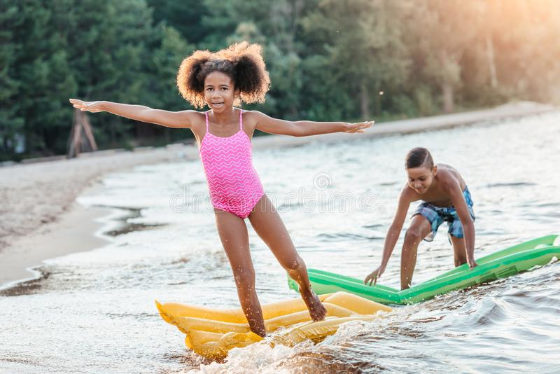 happy african american kids having fun with swimming mattresses stock images