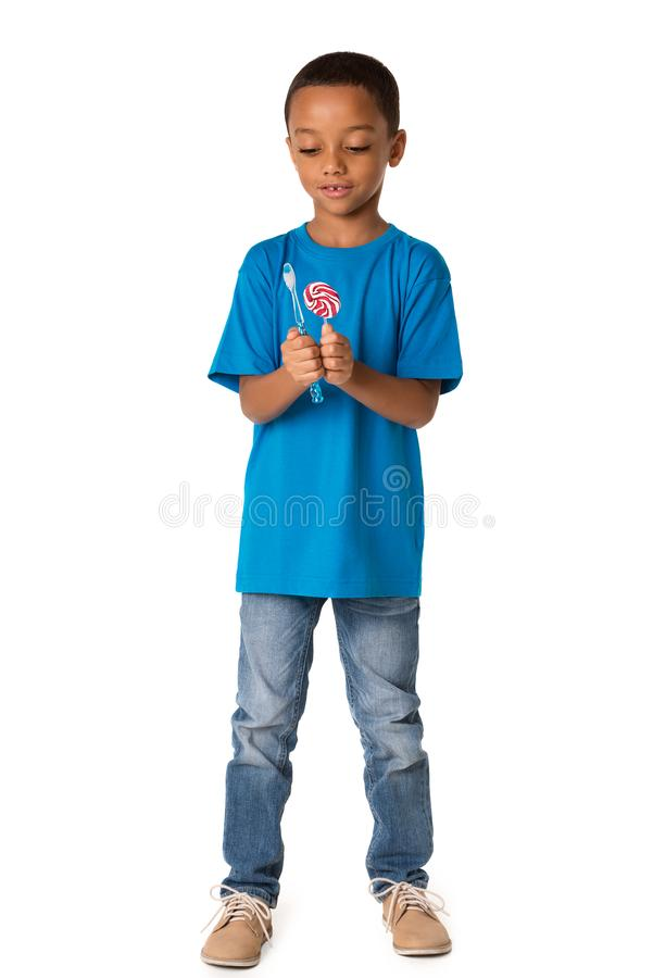 Happy african american little boy with toothbrush and sweet lolipop. Healthy teeth concept. royalty free stock photography