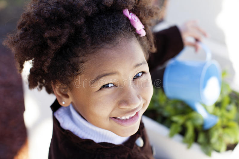 Happy african american little girl watering stock photo