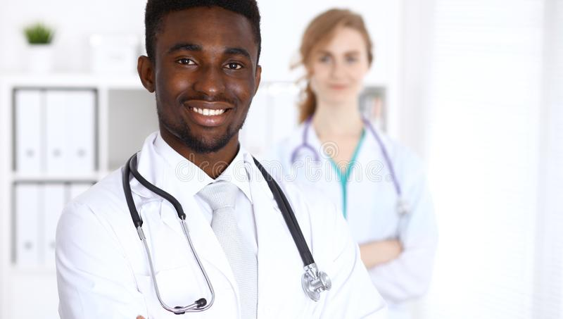 Happy african american male doctor with medical staff at the hospital. Medicine concept stock photos
