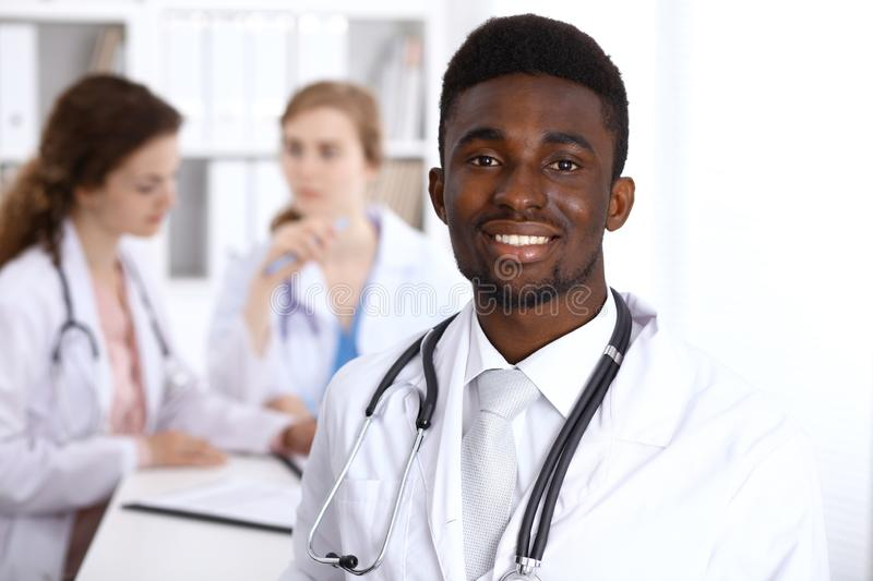 Happy african american male doctor with medical staff at the hospital. Medicine concept royalty free stock image