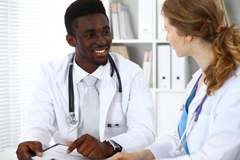 Happy african american male doctor with medical staff at the hospital. Medicine concept stock image