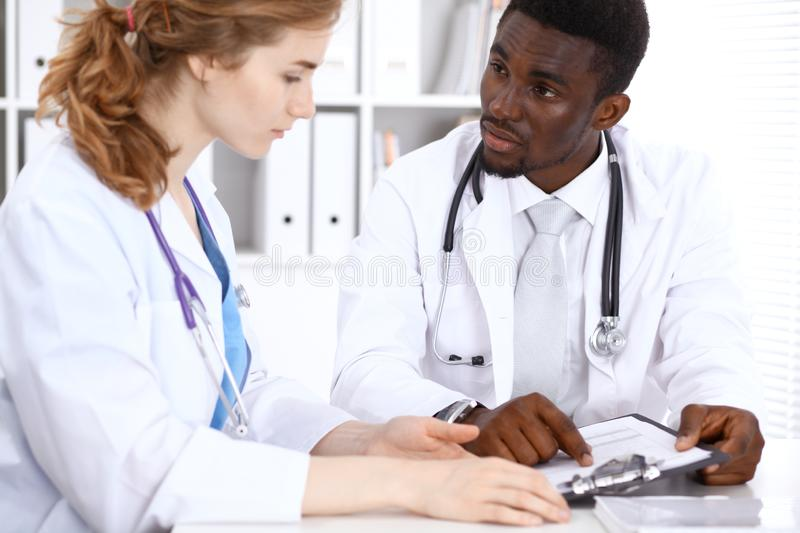 Happy african american male doctor with medical staff at the hospital. Medicine concept royalty free stock photos
