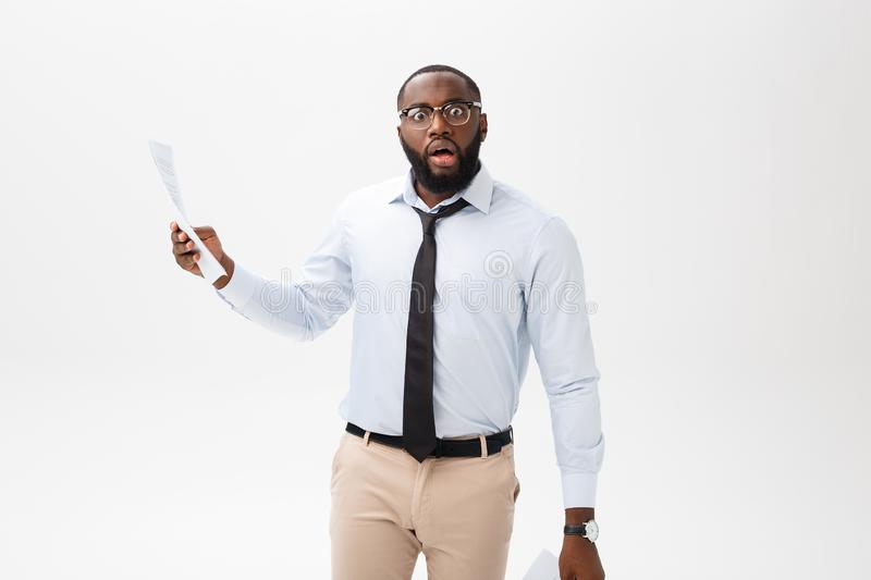 Happy African American man holding documaent paper over isolated white background with a surprise and shock face royalty free stock photos