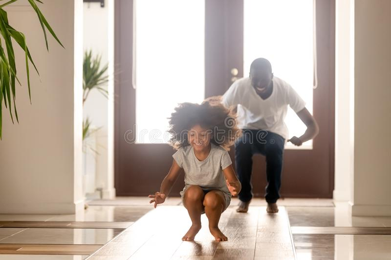 Happy African American man playing funny game with daughter at home royalty free stock images
