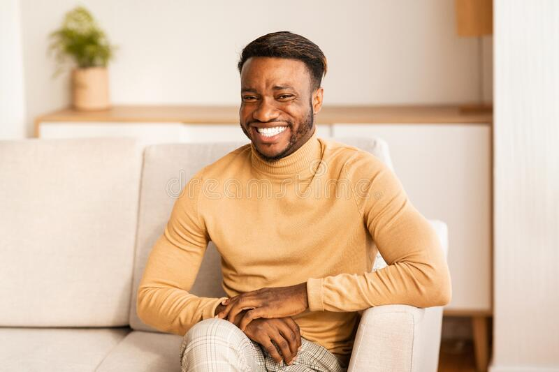 Happy African American Man Smiling Sitting On Sofa At Home royalty free stock images