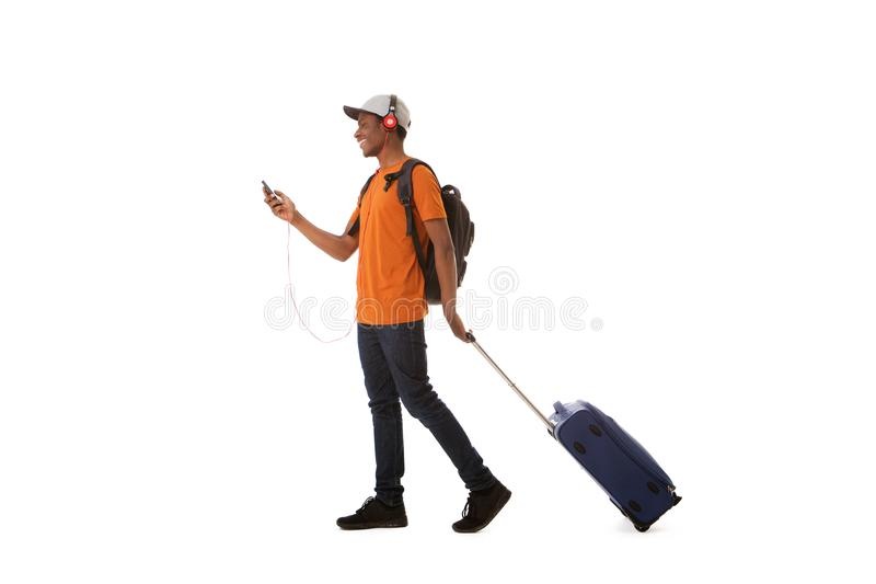 Happy african american man traveling with suitcase and listening to music with headphones and smart phone royalty free stock photos