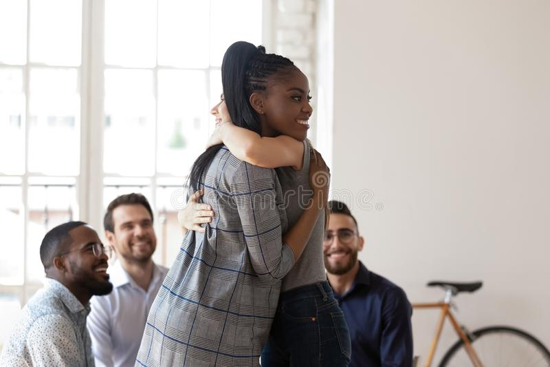 Happy african american manager hugging smiling female colleague. stock photo