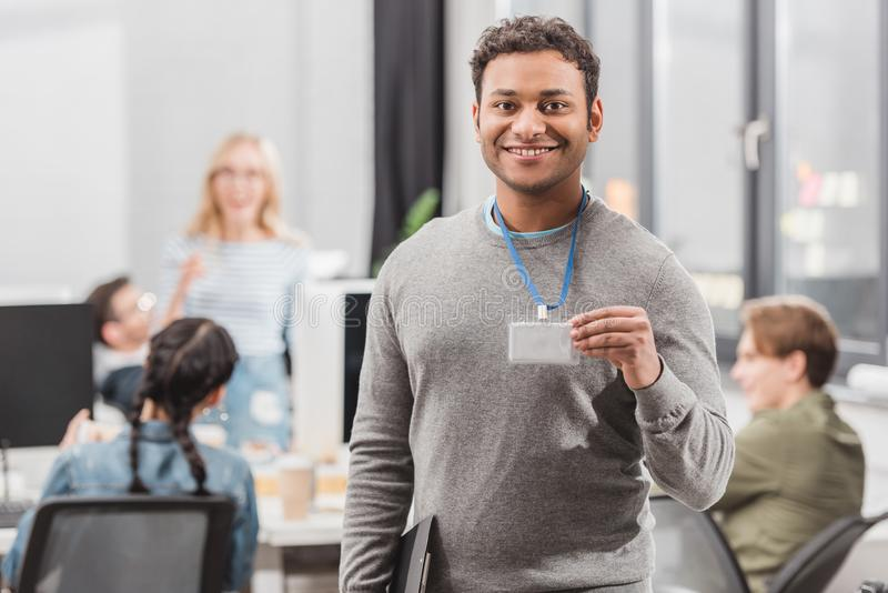 Happy african american man showing name tag. Happy african american men showing name tag at modern office royalty free stock image
