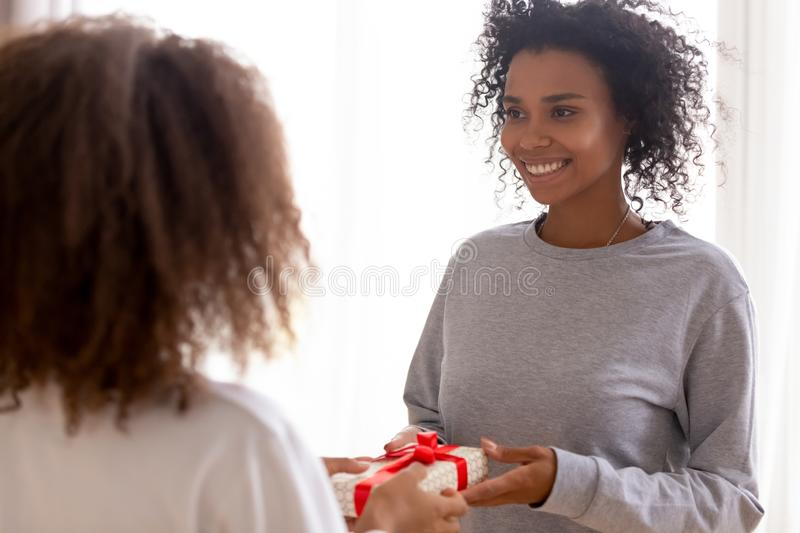 Happy African American mother receiving gift from teen daughter stock photo