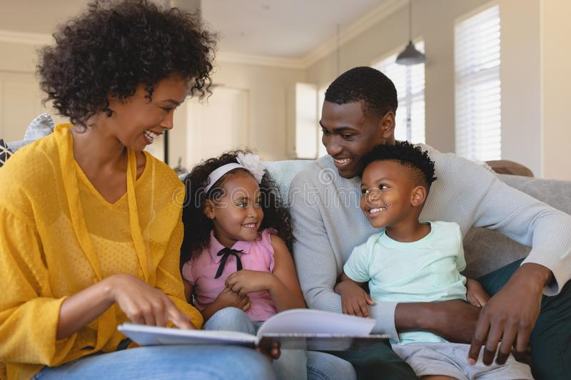 Happy African American parents with their cute children reading storybook on the sofa stock photography