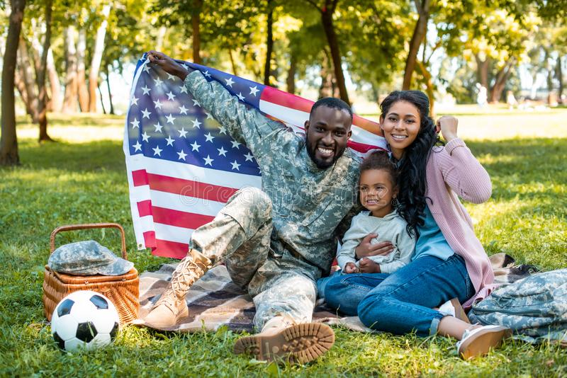 happy african american soldier in military uniform and family holding american flag vector illustration