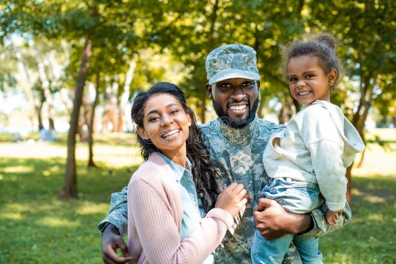 happy african american soldier in military uniform looking at camera with family stock photo