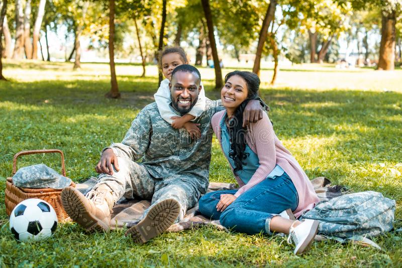 Happy african american soldier sitting on grass with family. In park royalty free stock photos