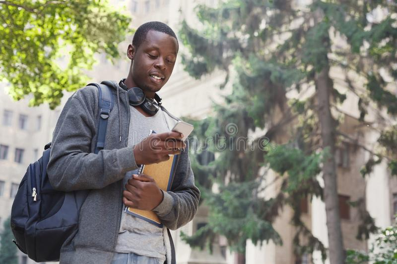 Happy african-american student texting in university campus stock image