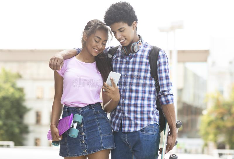 Happy african-american couple using smartphone while walking outdoors royalty free stock photography