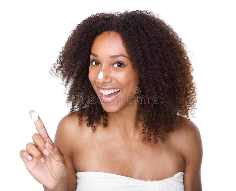 Happy african american woman with cream on finger and nose stock photo