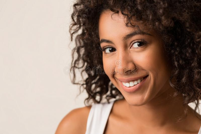 Happy african-american woman with curly afro hair stock images
